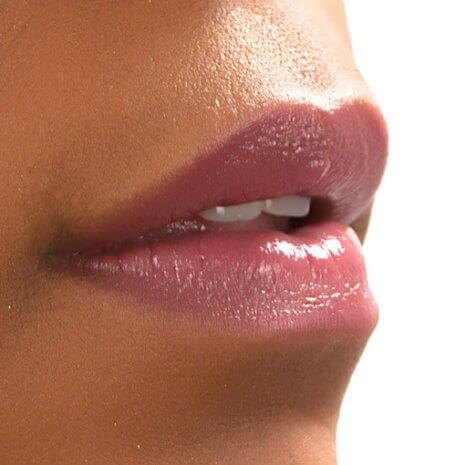 Close up image of model with dark skin tone wearing neutral pink lipstick Audrey by Red Apple Lipstick