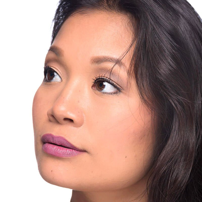 Image os women with dark brown almost black hair and medium skin tone wearing Oh Snapdragon Lipstick by Red Apple Lipstick. Oh Snapdragon is a soft blossom pink lipstick with cool-undertones of lavender