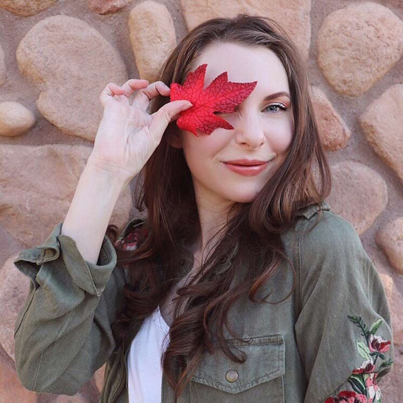 image of woman wearing lipstick for fall covering her right eye with a fall red leaf