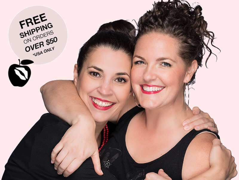 2 happy smiling women wearing allergy free red apple lipsticks.