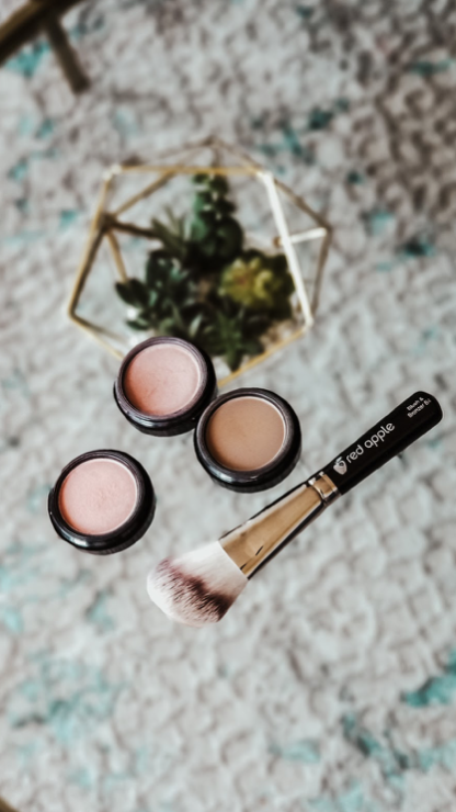 Image shows an angled blush brush by Red Apple lipstick, two open blush makeup products and one open bronzer makeup product