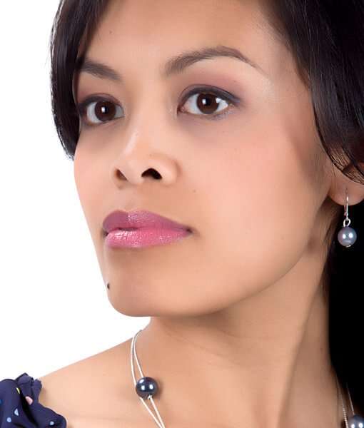 Image of women with black hair and medium skin tone wearing Maven Mauve Lipstick by Red Apple Lipstick.  Maven Mauve is a mauve, rose pink