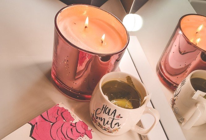 Image of a candle and a cup of tea. It's important to take some time to unwind for much needed self care.