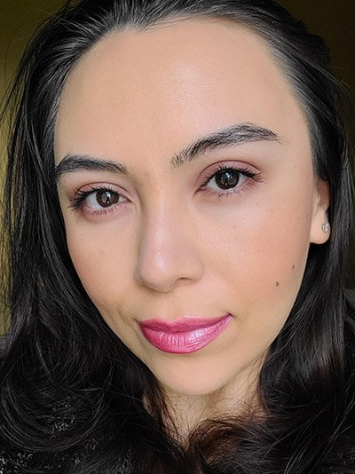 Image of female model with long black hair, dark eyebrows and dark brown eyes. She is wearing a beautiful glow of her makeup look using blush and bronzer to brighten and contour her face