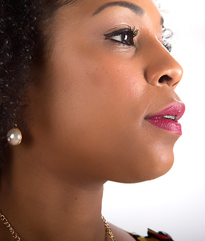 Image of lady with dark skin tone, black hair looking towards her left. She is shown wearing Hibiscus lipstick by Red Apple Lipstick. Hibiscus is a luscious and vibrant true raspberry color. A deep, berry pink with a hint of red.