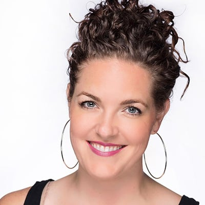 Image of lady with medium skin tone, blue eyes and brown hair pulled up to a loose bun. She is wearing Oh Snapdragon lipstick by Red Apple Lipstick. Oh Snapdragon is a soft blossom pink lipstick with cool-undertones of lavender that gives your lips a great kiss of color