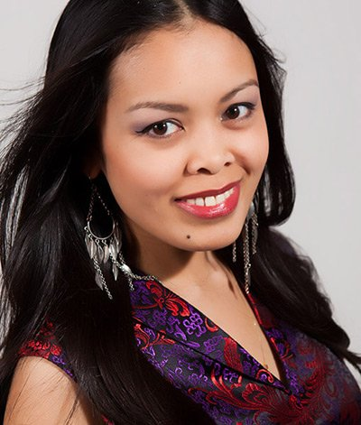 Image of lady with dark skin tone, long black hair and dark eyes. She is wearing lipstick in the shade called Barcelona. This is a mid-tone brownish red with the slightest orange undertones, has a beautiful satin finish.
