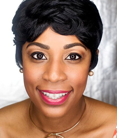 Image of lady with dark skin tone, short black hair and dark eyes, She is wearing lipstick in the shade called Bella Rina by Red Apple Lipstick. Bella Rina is a warm medium pink, a timeless classic color, perfect for those with warm undertones.