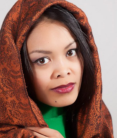 Image of lady with medium skin tone , black hair and dark eyes and a beautiful pashmina scarf around her head. She is wearing Fierce lipstick by Red Apple Lipstick. Fierce is a  deep Bordeaux red with rich purple and chocolatey undertones.