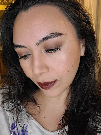 Image of lady with long black hair, medium complexion and is featured wearing Gypsy Soul lipstick by Red Apple Lipstick.  Gypsy Soul is a brick red with a brown undertone, makes a great brown lipstick color for medium skin tones with warm undertones.