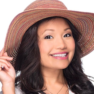 Image of lady with medium skin tone and long black hair and dark eyes wearing a summer hat. She is wearing lipstick in the shade called Let's Flamingle by Red Apple Lipstick. Let's Flamingle is a tropical hot pink with a coral cast. While this lipstick is a hot pink, it's on the softer side, making this sweet and sassy lipstick more versatile and not overly bright.