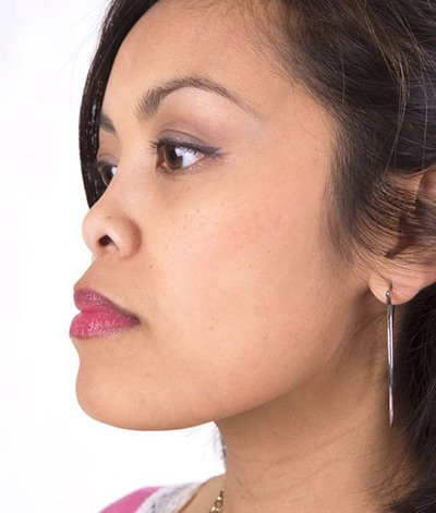 Image of lady with medium skin tone looking to her left with a side view showing her wearing lipstick in the shade called Love My Kiss by Red Apple Lipstick. This lipstick is the perfect middle ground between pink and red.