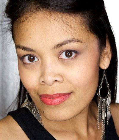Image of lady with medium skin tone, long black hair and brown eyes. She is wearing lipstick in the shade called Coral Crush by Red Apple Lipstick. Coral Crush is the epitome of a true coral color of pink and orange. It has a smooth, satin finish which produces a lovely sheen, without any glitter, frost or shimmer