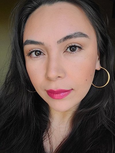 Image of lady with medium skin tone, long black hair and dark eyes wearing lipstick in the shade called Hibiscus by Red Apple Lipstick. A deep, berry pink with a hint of red to it, a true raspberry color.