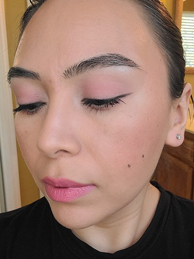 Image of female with light to medium skin tone, Black Hair, Dark eyebrows and dark brown eyes. Pink shades for eyeshadows, Pink shades of blush on her cheeks and Mauve Me Lipstick .She is looking slightly to her right and down to show the color on her eyelids with pink monochromatic makeup