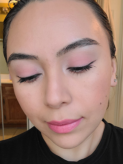 Image of female with light to medium skin tone, Black Hair, Dark eyebrows and dark brown eyes. Pink shades for eyeshadows, Pink shades of blush on her cheeks and Mauve Me Lipstick. She is looking straight on but eyes downward to show off the beautiful pinks in her monochromatic makeup look