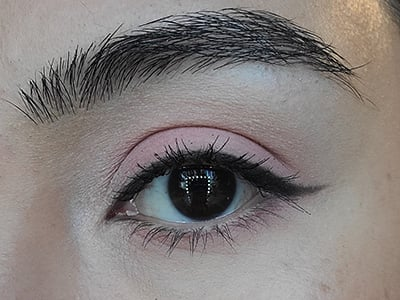 Image of a female eye with dark brown eyes completing the monochromatic pink makeup look having applied The Lash Project mascara.