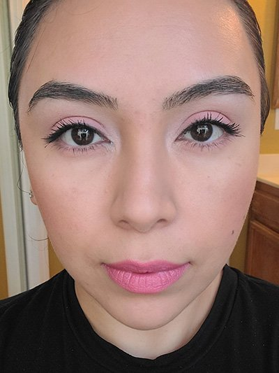 Image of female with light to medium skin tone, Black Hair, Dark eyebrows and dark brown eyes. Pink shades for eyeshadows, Pink shades of blush on her cheeks and Mauve Me Lipstick