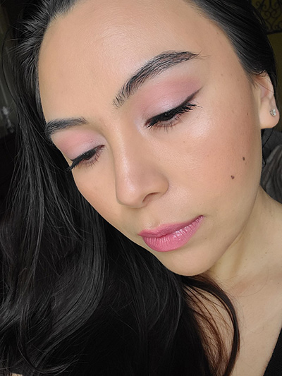 Image of female with long black hair wearing Red Apple lipstick in the shades Porcelain, On Pointe, Tutu Cutie, and Innocence with Black Eyeliner Pencil topped with Black Magic eyeshadow too. On her face she is wearing Sundrop Bronzer and M'Lady Blush showing wedding makeup tips