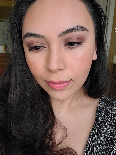 Image of female with long black hair, dark brown eyes wearing Red Apple Lipstick's Lipstick in the shade called Maven Mauve topped with Honey Badger Lip Gloss