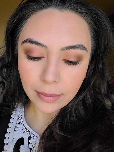 Image of female with long black hair wearing Red Apple Lipstick eyeshadows in the shades Porcelain, She's Spicy, Hush Hush, and Brownie Points. The Lash Project Mascara , Sundrop Bronzer and Tango Blush