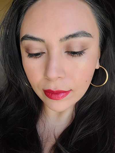 Image of female with long black hair wearing Red Apple Lipstick's Lipstick in the shade called Risque and Almost Red Lip Liner