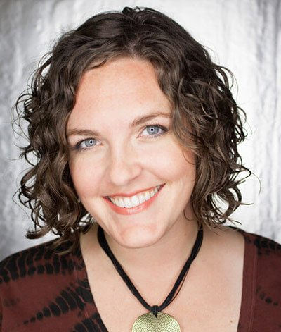 Image of lady with light to medium skin tone, gray blue eyes with short curly brown hair. She is wearing Beachside lipstick by Red Apple Lipstick