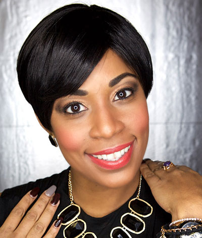 Image of lady with dark skin tone, dark eyes and short black hair. She is wearing Coral Crush Lipstick by Red Apple Lipstick