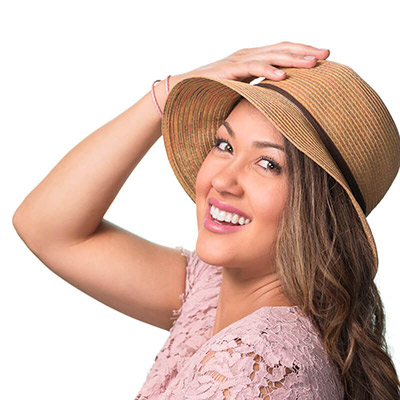 Image of lady with medium warm skin tone with a summer hat on and looking towards the side. She is wearing Let's Flamingle lipstick by Red Apple Lipstick