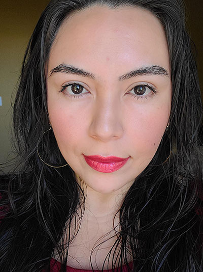 Image of lady with long black hair, dark eyes wearing Sundrop Bronzer, Gotta Glow blush, The Lash Project mascara and Risque Lipstick all by Red Apple Lipstick