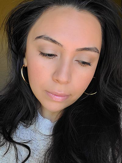 Image of lady with long dark hair, dark eyes and brows with medium skin tone. She is featured here looking to her left and head tilted slightly downward after completing the Ethereal and Natural Summertime makeup look. All with Red Apple lipstick products.