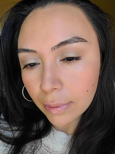 Image of lady with long dark hair, dark eyes and brows with medium skin tone. She is featured here looking to her right and eyes looking downward after completing the Ethereal and Natural Summertime makeup look. All with Red Apple lipstick products.