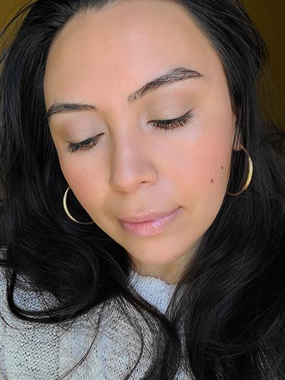 Image of lady with long dark hair, dark eyes and brows with medium skin tone. She is featured here with her eyes looking down to show the eye lid colors used and after completing the Ethereal and Natural Summertime makeup look. All with Red Apple lipstick products.