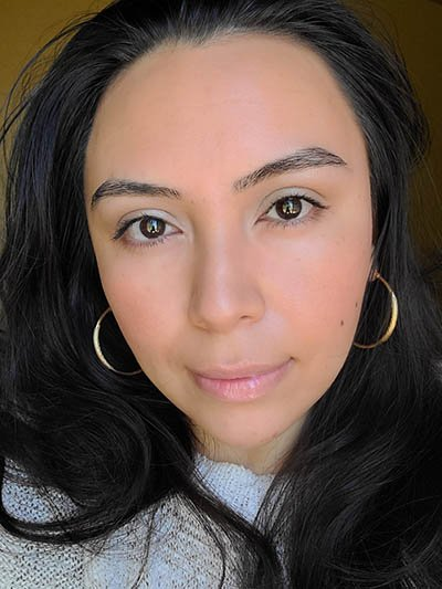 Image of lady with long dark hair, dark eyes and brows with medium skin tone. She is featured here looking straight on after completing the Ethereal and Natural Summertime makeup look. All with Red Apple lipstick products.