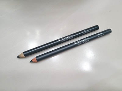 Image of the Black and Charcoal eyeliner pencils by Red Apple Lipstick. Both are laying side by side with the cap off and pencil tip sharpened.
