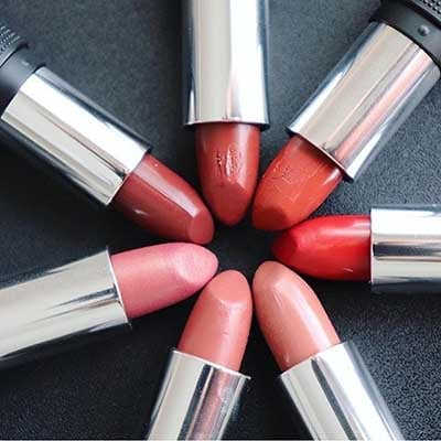 Image of 7 Red Apple Lipstick tubes with bullet's twisted up and caps off laying in a circular pattern showcasing some colors that would make a great cream blush if preferred