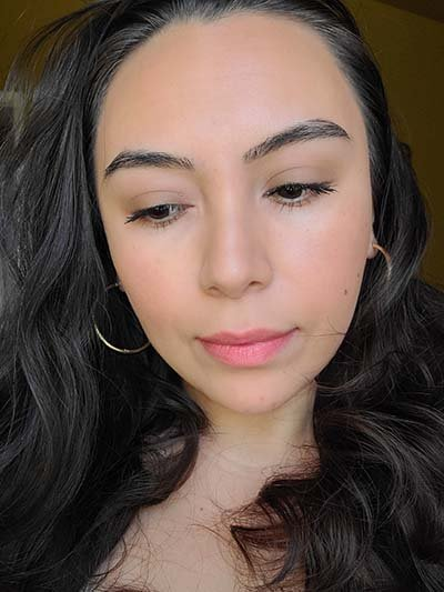 Image of lady with medium skin tone, long dark hair and dark eyes. She is wearing a  light makeup application of Prime Time primer on the lids, Heirloom, Blondeshell, and Buttercream eyeshadows and The Lash Project mascara on the eyes; Sundrop Bronzer and Tango Blush; wearing Coral Crush lipstick as a lip stain. All products featured are from Red Apple Lipstick INC