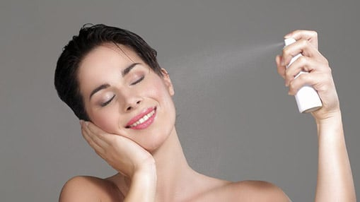 Image of stock model showing herself spraying a facial mist onto her face with her head tilted to the right and her cheek in the opposite palm of her hand