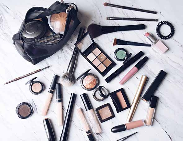 Image of makeup products and a makeup bag as a part of post talking about what to do with expired makeup and if it is bad to use expired makeup.